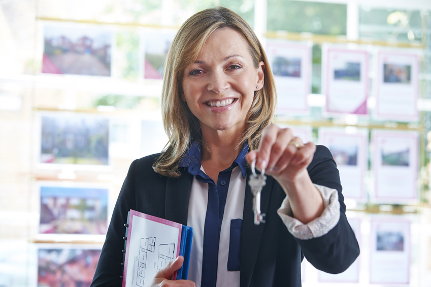 photo : Estate Agent In Office Holding Keys To Property