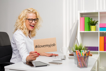 "photo : Woman in office showing ""I love my job"" cardboard"
