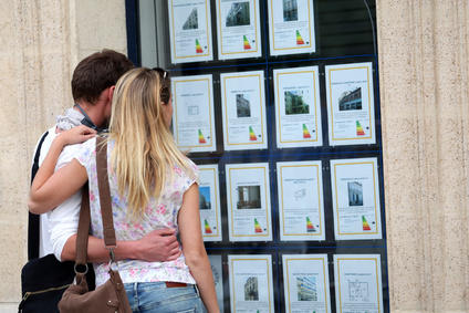 photo : Couple looking at house-for-sale ads through shop window