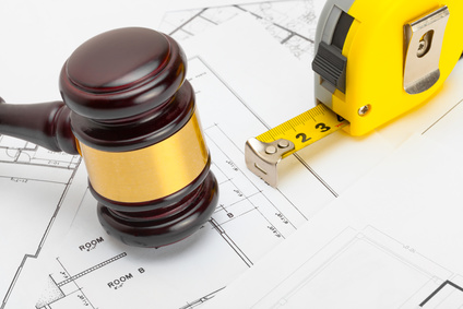photo : Judge gavel with measure tape above construction blueprint