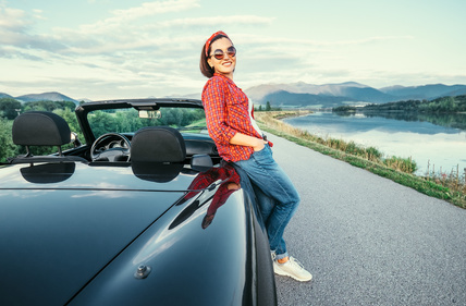 photo : Young woman stand near cabriolet car on the  road with beautiful mountain lake view