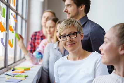 photo : lächelnde frau arbeitet im team in einem workshop
