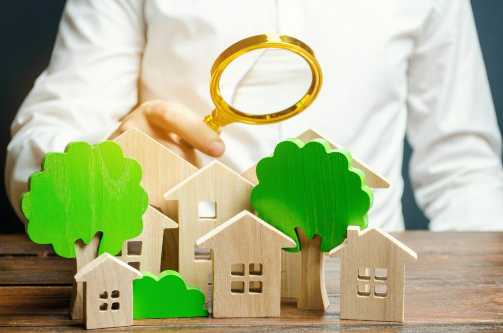 photo : A man holds a magnifying glass over wooden houses and trees. Real estate valuation and selection of a place for the construction of new buildings. Evaluation of urbanism and residential space.