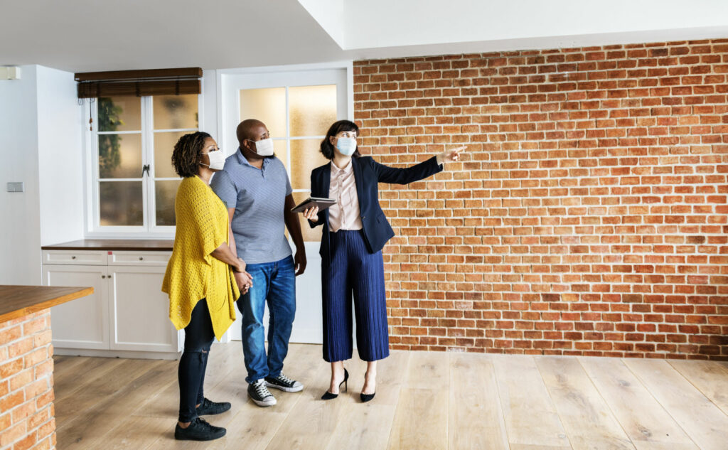 photo : Real estate agent and customer in face mask looking at a new project