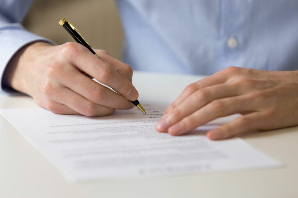 photo : Successful male entrepreneur signing contract agreement, bank loan form.