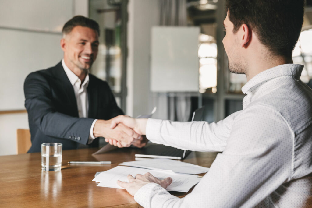 photo : Business, career and placement concept - successful young man smiling, and handshaking with european businessman after successful negotiations or interview in office