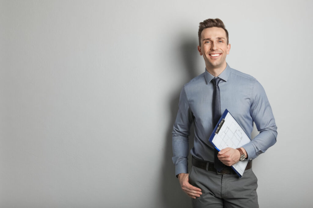 photo : Male real estate agent with clipboard on grey background