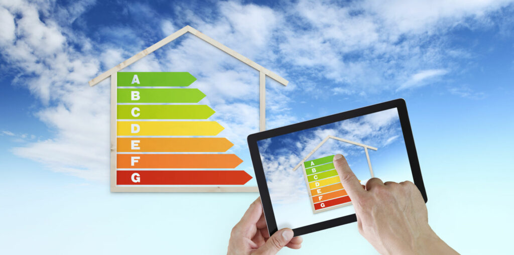 photo : hand touch screen of digital tablet with house shape and energy efficiency chart symbol, isolated on blu sky background, green buildings and save energy eco sustainability