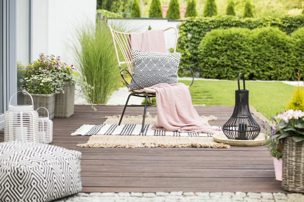 photo : Real photo of a white pillow and pink blanket on a rattan chair standing in the garden of a luxurious house