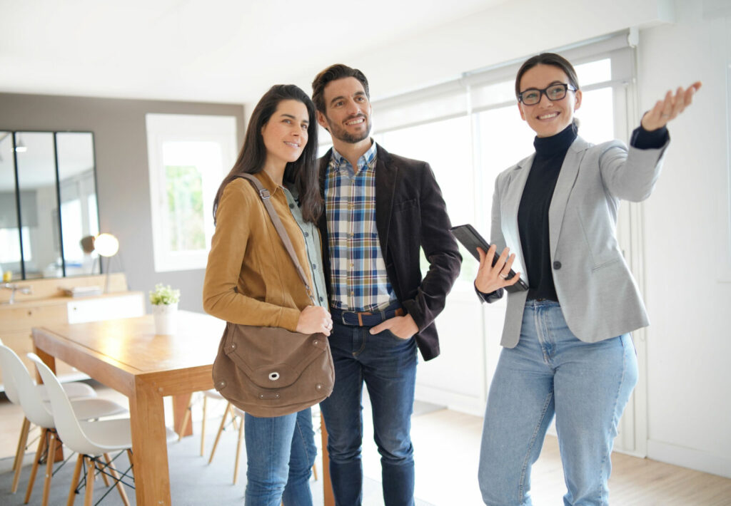 photo : Real estate agent showing modern house to attractive couple
