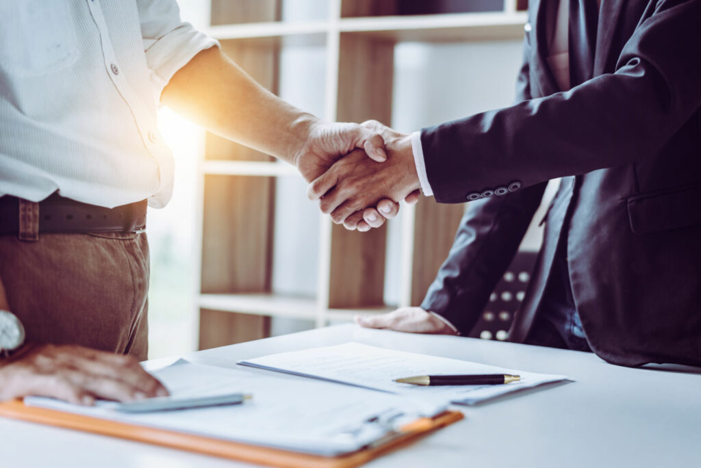 photo : Middle age Asian partner lawyers attorneys shaking hands after discussing a contract agreement done.