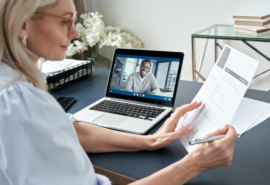 photo : Female hr reading cv during online virtual job interview by video call.