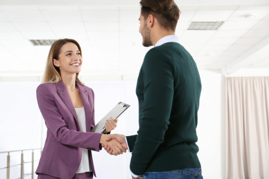 photo : Real estate agent shaking hands with client in new apartment