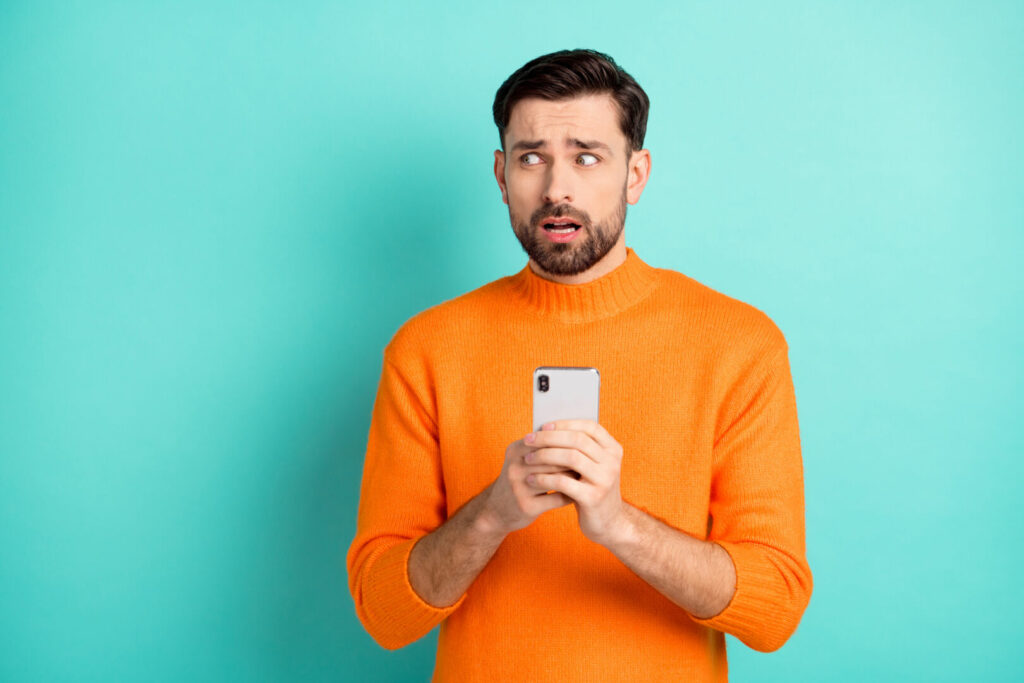 photo : Photo of young man afraid scared nervous use cellphone look empty space fail problem isolated over turquoise color background