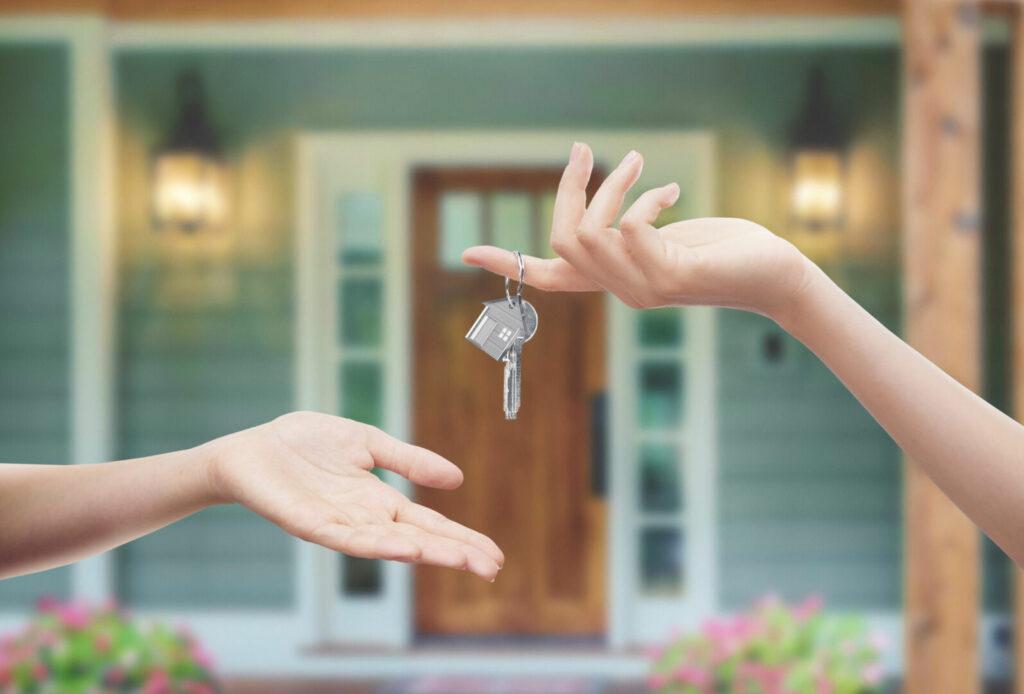 photo : Mani con chiavi con sfondo porta di casa