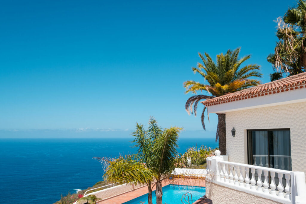 photo : house with swimming pool, palm trees and ocean sea view