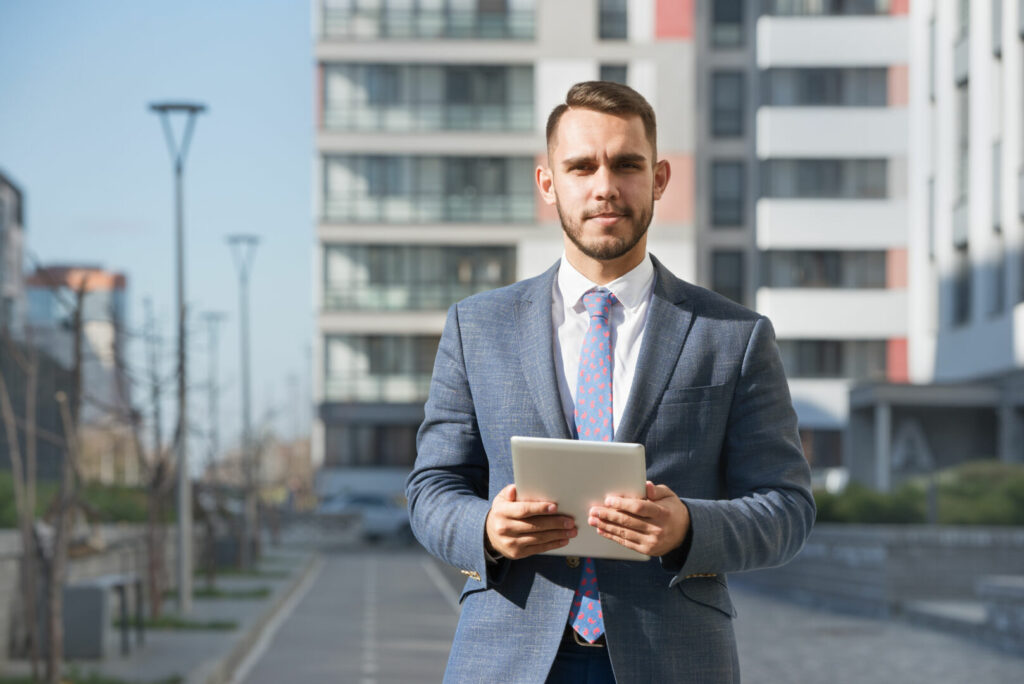 photo : Businessman or real estate agent with tablet computer against new building
