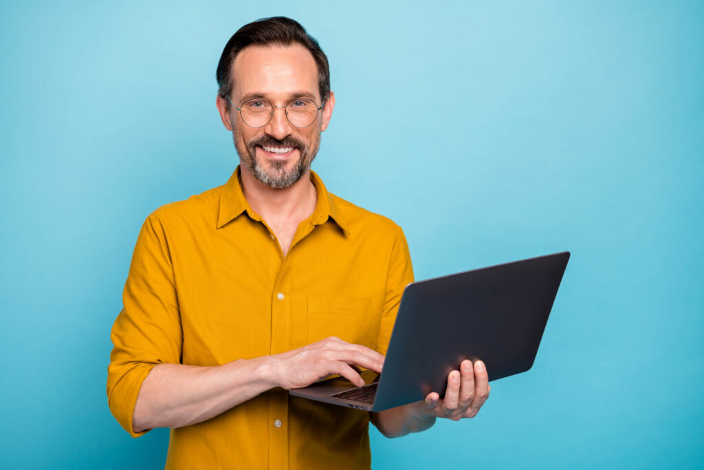 photo : Portrait of positive cool mature man hold his computer work text type chatting with family colleagues wear good looking clothes isolated over blue color background