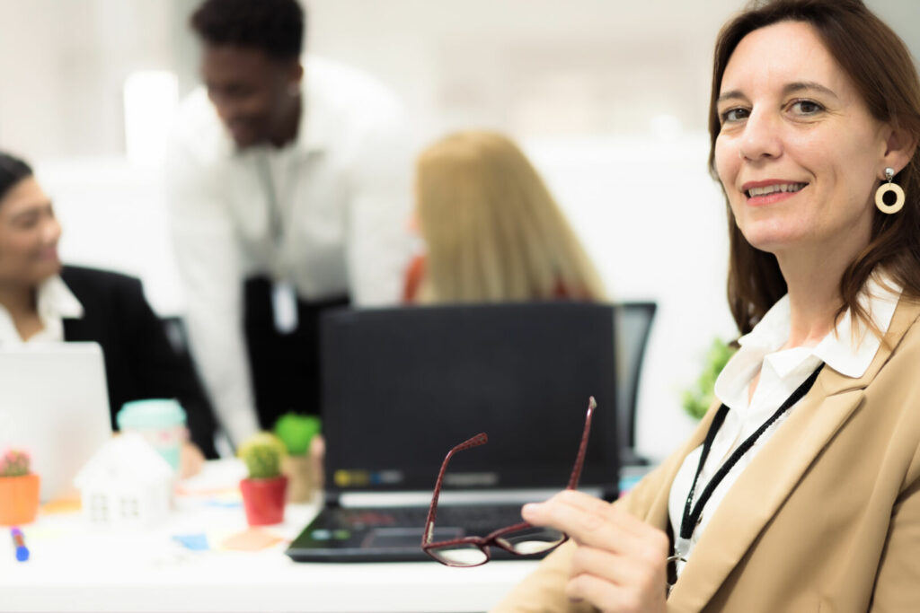 photo : Portrait of young female teacher at desk looking to camera.  .Employees working at computers in office with general manager. Job, study and Technology concept.