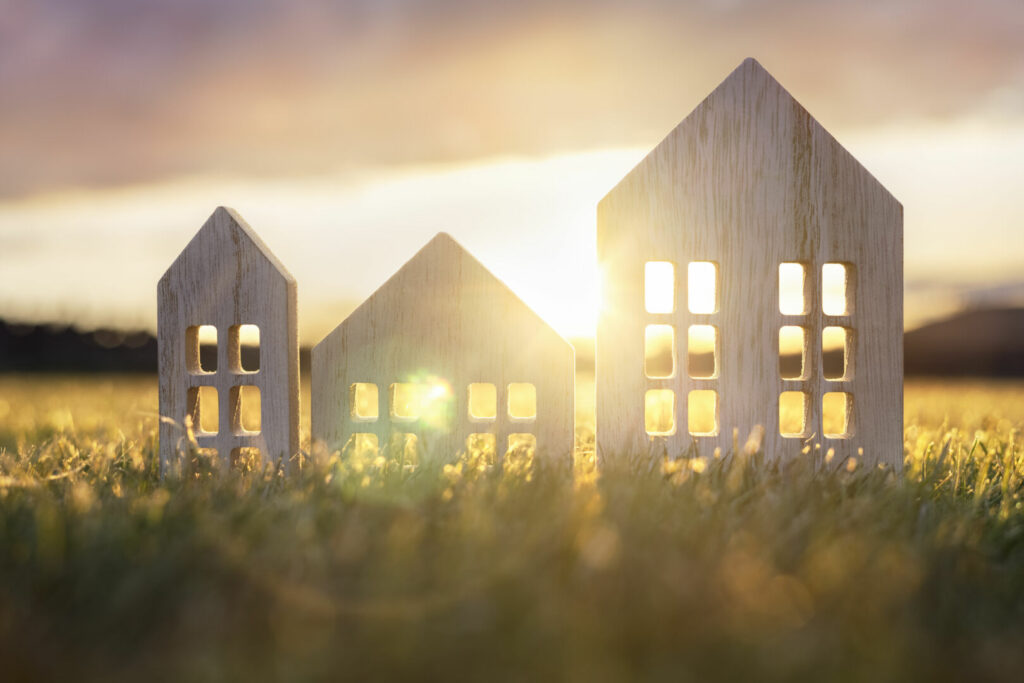 photo : Ecological wood  model house in empty field at sunset