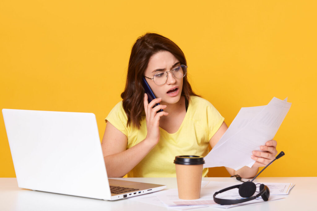 photo : Close up portrait of business woman working online via laptop, isolated over yellow studio background, talking to somebody via smart phone, holding paper in hands, looks astonished. and concentrated.
