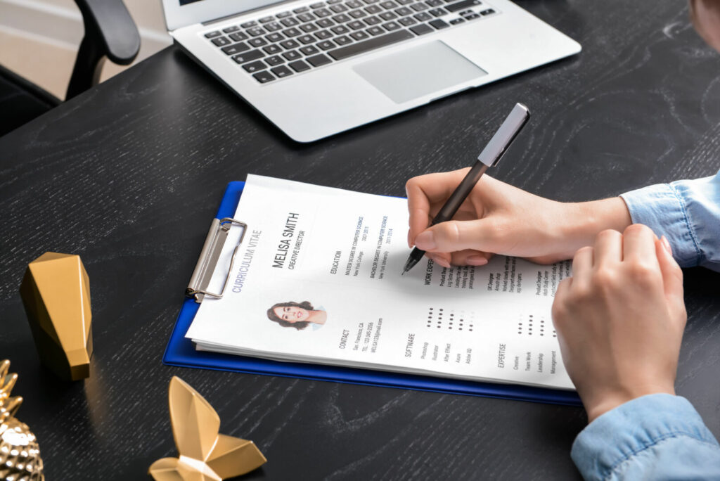 photo : HR manager studying job resume of candidate at table
