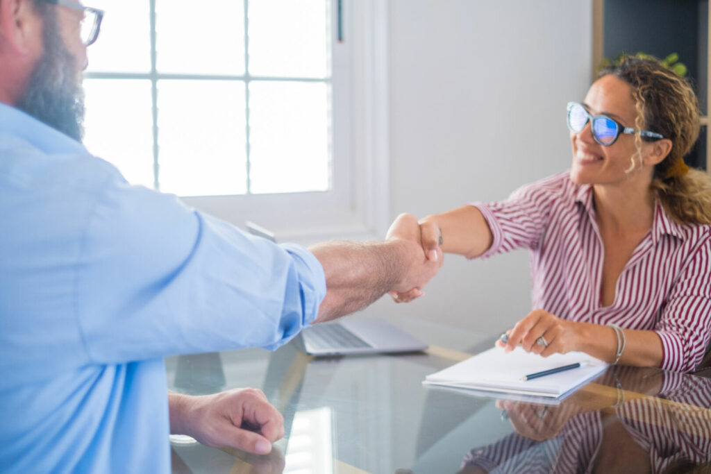 photo : Smiling caucasian female hr manager handshake hire male candidate at job interview make good first impression, happy mixed race client shake hand of bank broker, respect, business agreement concept.