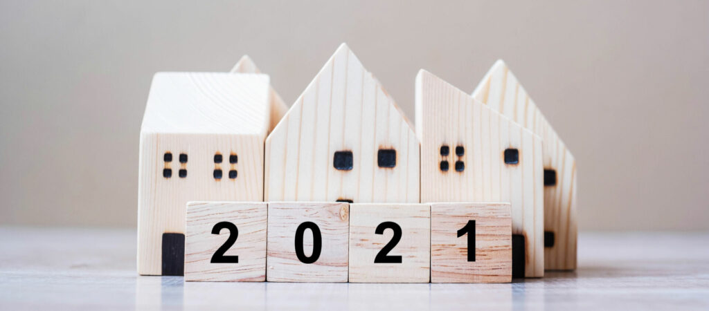photo : 2021 Happy New Year with house model on table wooden background. Banking, real estate, investment, financial, savings and New Year Resolution concepts