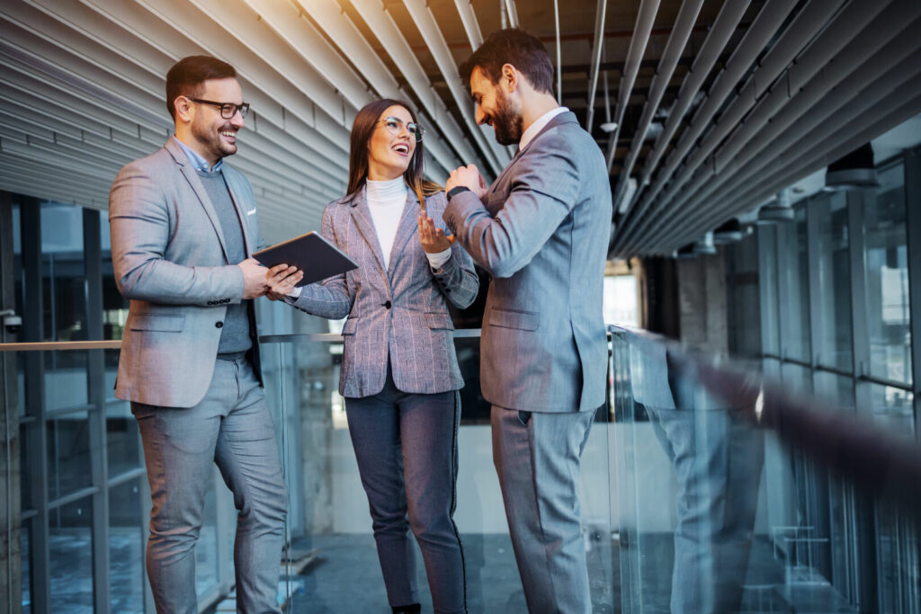 photo : Group of cheerful caucasian elegant dressed real estate agents standing in the building in construction process and chatting. They taking a break form hard work. Woman in the middle holding tablet.a