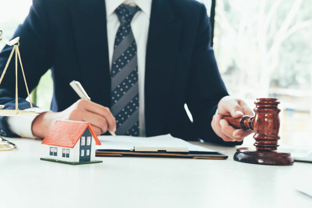 photo : Real Estate Law concept. Gavel on sounding block in hand's Male judge at a courtroom, working for the insurance compensations. report the case on table in modern office.